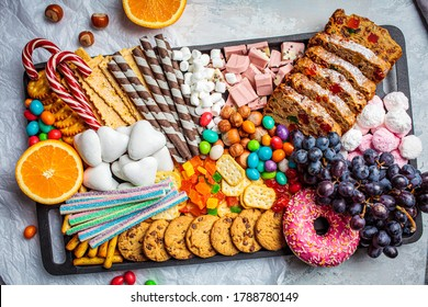 Christmas sweets platter. Christmas fruit cake, candy, chocolate, candy cane, cookies, fruit on black tray. Christmas food concept.