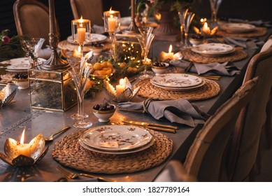 Christmas table with candles, flowers and fruits