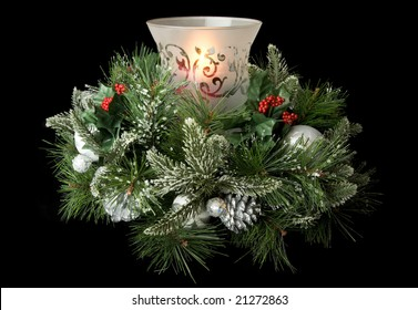 Christmas table centerpiece with hurricane glass, glowing candle and frosted greenery, isolated on black