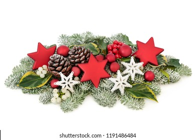 Christmas table decoration with bauble decorations, holly berries, snow covered spruce pine, ivy, pine cones and mistletoe isolated on white background.