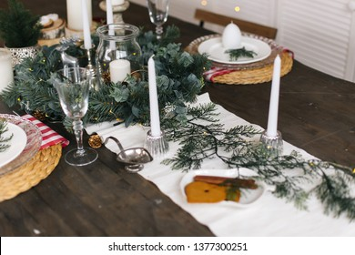 Christmas table decorations with ginger bread hearts bisсuits, tree brunches, fir apples and lights