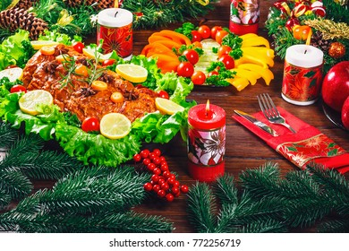 Christmas table dinner time with roasted meats, candles and New Year decor. Background thanksgiving. The concept of a family holiday, Beautiful delicious food