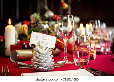A christmas table is laid with place settings, decorations and candles ready for christmas lunch