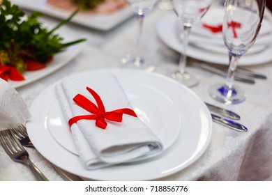 Christmas table layout, red tape with a cinnamon stick, rosmarin and a slice of dry orange on the dark wooden background with christmas decorations