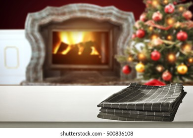 christmas table place with napkin and background of fireplace and xmas tree