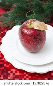 Christmas table place setting with a decorative apple on red napkin