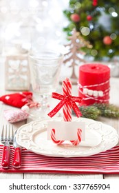 Christmas table place setting. Elegant empty plate, cutlery, napkin and blank name card on candy cane stand.