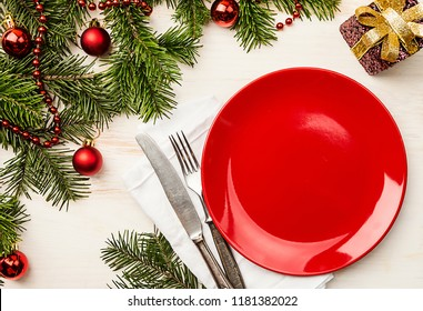 Christmas table place setting with empty red plate and cutlery with festive decorations, fir tree and balls. New Year holiday background, top view