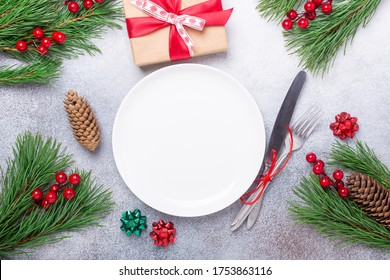 Christmas table place setting with empty white plate, gift box, cutlery with festive decorations star bow ball on stone background. Christmas and New Year holiday concept - Image