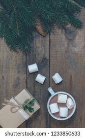 Christmas table place setting. Holidays background. Hot chocolate with marshmallow, Christmas gift and spruce branch with cones on dark wooden surface.