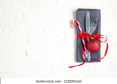 Christmas table place setting with knife, fork, red ball, candy cane and ribbon over white table with copyspace.