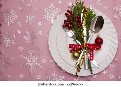 Christmas table place setting with pine branches,ribbon and bow.