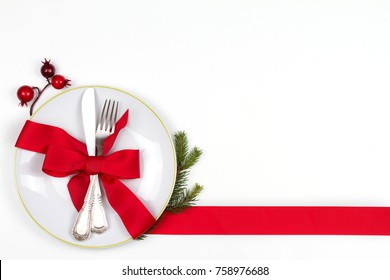 Christmas table place setting with plate, cutlery, pine branches,  ribbon and red berries. Winter holidays and festive background. Christmas eve dinner, New Year food lunch. View from above, top