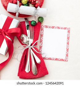 Christmas Table Place Setting in Red, White and Silver with Silverware, a gift, and party cracker on White Cloth Background with room or space for copy, text or your words.  Square with above view