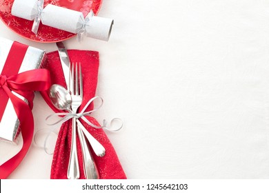 Christmas Table Place Setting in Red, White and Silver with Silverware, a gift, and party cracker on White Cloth Background with room or space for copy, text or your words.  Horizontal with above view