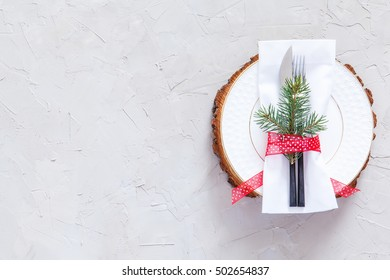 Christmas table place setting. Christmas serving cutlery with napkin, plate and logs cut on a concrete background. Christmas and New Year holidays background