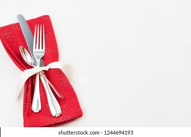 Christmas Table Place Setting with Silverware, Red Cloth Napkin on White Tablecloth Background with blank room or space for copy, text or your words.  Horizontal flaylay with above, looking-down view.