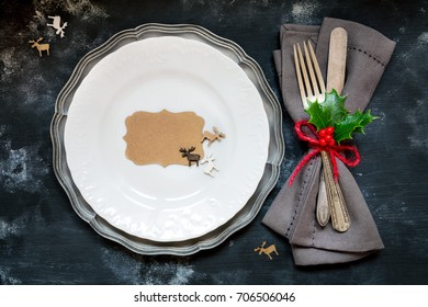 Christmas table place setting with vintage silverware decorated with festive holly leaves and plate with an empty tag on rustic wooden background