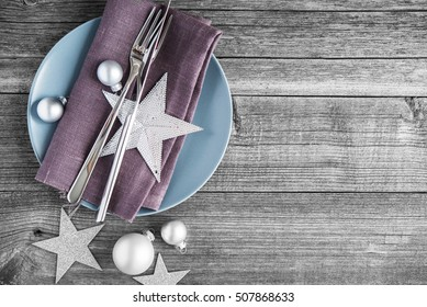 Christmas table place setting with xmas decorations on old wood background. Merry christmas card. Winter holiday theme. Happy New Year. Space for text.