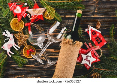 Christmas table serving, and a bottle of wine. New Year. Christmas tree and Christmas tree decorations. On a wooden background. Free space for text.