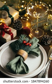 Christmas table setting among gift boxes and garland lights on wooden table. Concept of Christmas and New Year dinner.