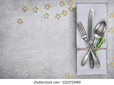 Christmas table setting background with copy space. Concrete background with napkin, silverware and rosemary branch. Cutlery with fork, knife and spoon. Top view, christmas decoration.