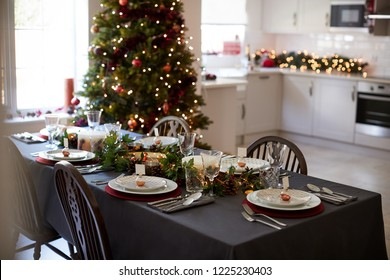 Christmas table setting with bauble name card holders arranged on plates and green and red decorations with Christmas tree and kitchen in the background