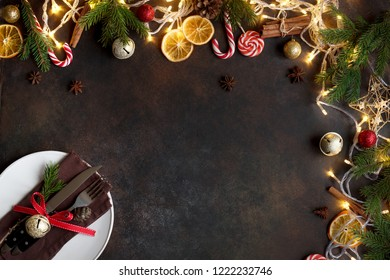 Christmas table setting and border with lights, golden balls, fir branches on dark background with copy space.
