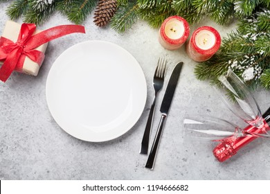 Christmas table setting with champagne, gift box and fir tree branch covered by snow on stone background. Top view with space for your greetings