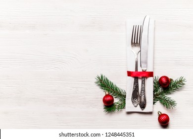 Christmas table setting conceptual design with fork, knife and festive attributes. New Year banquet serving appointment options with silverware. Background, close up, top view, flat lay, copy space.