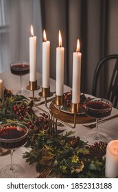 Christmas table setting with decorations and candles.