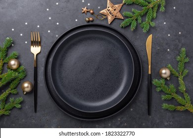 Christmas table setting with empty black ceramic plate, fir tree branch and gold accessories on black stone background. Top view. Copy space - Image