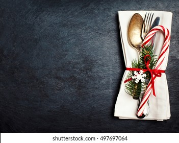 Christmas table setting with festive decorations on white tablecloth over black  background with copy space.