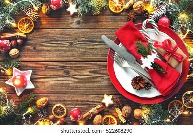 Christmas table setting with fir tree, oranges, cones, nuts, spices, cookies and lights on a wooden table