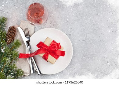 Christmas table setting with gift box and fir tree branch covered by snow on stone background. Top view with space for your greetings