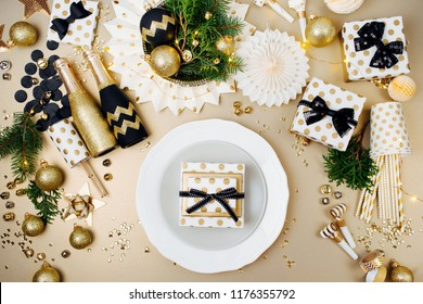 Christmas table setting. Gold and black decoration with with gift and fir-tree branch. Flat lay, top view.
