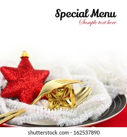 Christmas table setting with ornaments on a plate