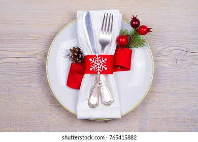 Christmas table setting with plate, cutlery and red ribbon. Winter holidays and festive background. Christmas eve dinner, New Year food lunch. View from above, top, horizontal