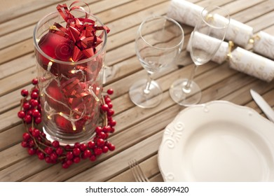 Christmas table setting with red decorations and berries on a slatted wood table ready to celebrate the holiday season