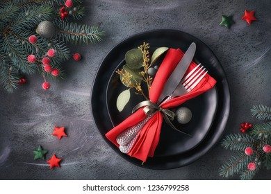 Christmas table setup on dark background. Flat lay with Xmas decorations in green and red with frosted berries, trinkets, black plates and crockery.