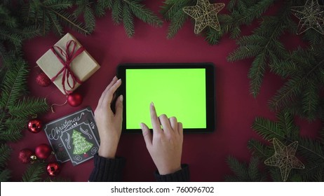 Christmas table top view from above. Tablet with green screen. Woman slide images and zooming. Different gestures. Red background with garland. Chroma key
