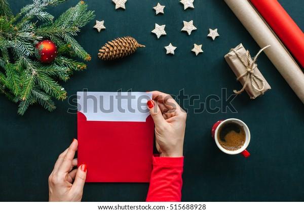 Table de Noël avec différents objets. Les mains de la femme qui met une lettre dans une enveloppe