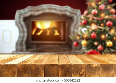 christmas table of wood with free space for your decoration and background of fireplace and xmas tree