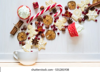 Christmas tea cup with gingerbread cookies and other sweets on white wooden background. Top view