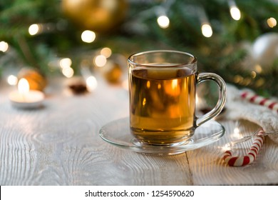Christmas tea in glass cup . composition with candle, pine branches, pine cones and candle on background of garlands on wooden table