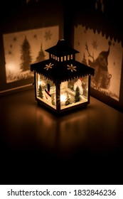 Christmas tea light candle lantern with snowman cast shadows of christmas trees and snow flakes