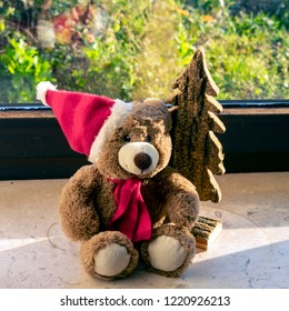 Christmas teddy bear with christmas tree on the windowsill
