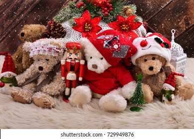christmas teddy bears in santa claus outfits with decorations and old toys sitting  against wooden background