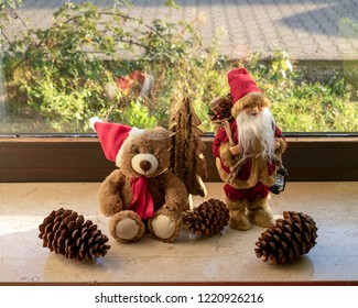 Christmas teddy and Santa Claus with decorations on the windowsill