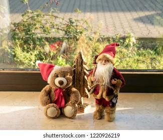 Christmas teddy and Santa Claus on the windowsill